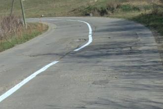 """Soluția găsită de un muncitor de la """"drumuri"""" pentru o șosea plină de gropi. Cum a fost trasat marcajul"""