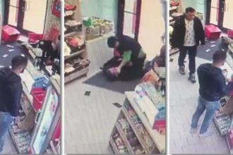Momentul în care o vânzătoare se luptă cu hoții, în magazin, în timp ce 2 bărbați se uită