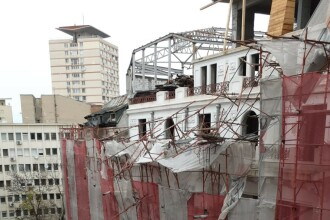 O schelă s-a desprins parțial de pe fațada unui bloc din București. Două mașini avariate