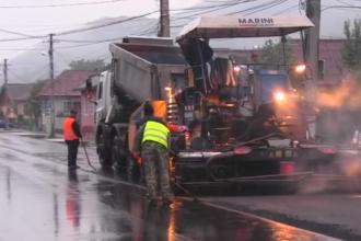 Asfaltare pe ploaie in orasul Dej. Motivul pentru care muncitorii au turnat tone de asfalt pe o strada cu balti. VIDEO