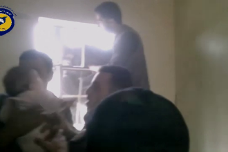 Imagini emotionante filmate in infernul din Siria. Un bebelus blocat in casa a fost salvat prin grilajul unei ferestre