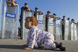Imaginea zilei: un copilas sirian, in fata cordonului de politie, in Turcia. Sute de refugiati, blocati la granita cu Grecia