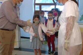 Tabloul începutului de an școlar, în vreme de pandemie. Copiii cu mască la gură, duși cu sfoara în clasă