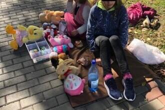 Două fetițe din Roman își vând plângând jucăriile pe stradă pentru ca părinții să aibă bani de facturi
