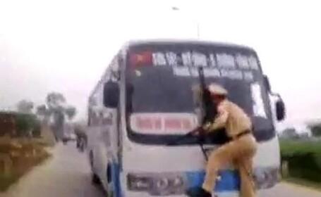 Imaginile zilei. Un politist se agata de stergatoarele unui autobuz pentru a opri un sofer nebun