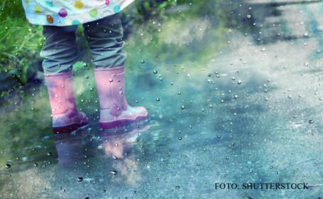 ploaie, copil care se joaca in balti FOTO SHUTTERSTOCK