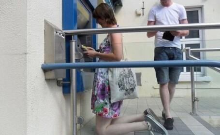Bancomatul in fata caruia clientii trebuie sa stea in genunchi pentru a scoate bani. FOTO