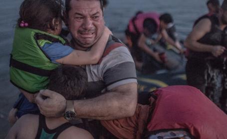 Un tata sirian plange, tinandu-si copiii la piept, dupa ce ajunge pe tarmul insulei Kos. Povestea unei fotografii-simbol
