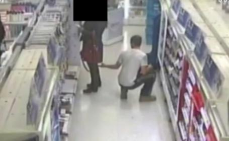Momentul in care un barbat e surprins de camere in timp ce face poze sub fusta unei femei, intr-un magazin din Londra