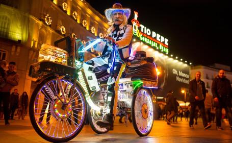 Un artist stradal merge cu bicicleta sa luminata, in Madrid, inaintea deschiderii targului de Craciun