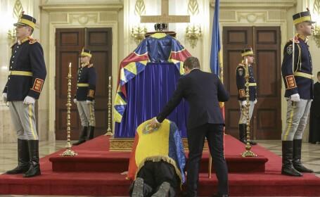 O persoana plange in genunchi in fata sicriului Regelui Mihai I care este depus la Palatul Regal din Bucuresti