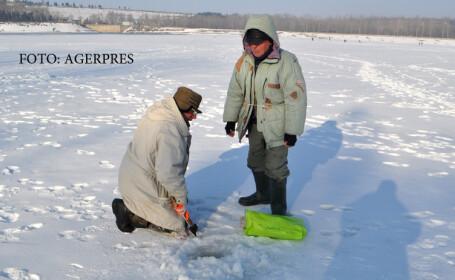 Doua persoane pescuiesc la copca la Barajul Stanca-Costesti.