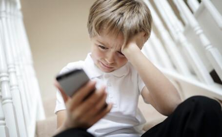 copil speriat cu un telefon in mana