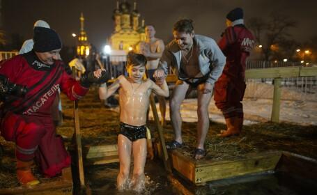 Un băiat este ajutat să facă o baie în apă înghețată, de Bobotează, în Moscova