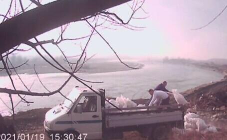 Doi bărbați, filmați în timp ce aruncă zeci de saci cu moloz pe malul Jiului. Polițiștii îi caută