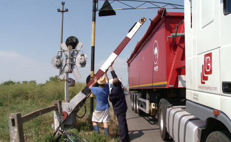 Un sofer a ignorat semnalele de la o trecere de cale ferata si s-a blocat cu TIR-ul sub bariera.FOTO