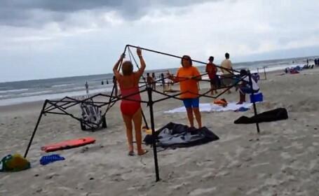 Moment amuzant pe o plaja din SUA. Doua femei sunt prinse in timp ce incearca sa fure un baldachin