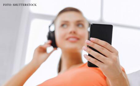 tanara care asculta muzica de pe telefon la casti