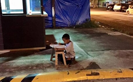 Imaginea care a induiosat internetul: baiatul de 9 ani care isi face temele in strada, la lumina reclamei unui fast-food