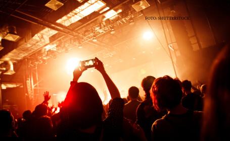 tineri care filmeaza cu telefoanele la un concert