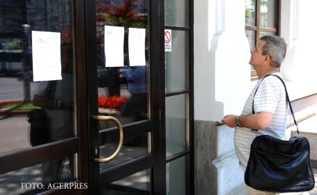 Un barbat priveste un anunt afisat de functionarii Primariei Sectorului 3 Bucuresti care au intrat, marti dimineata, in greva generala, in semn de protest fata de nivelul scazut al salariilor.