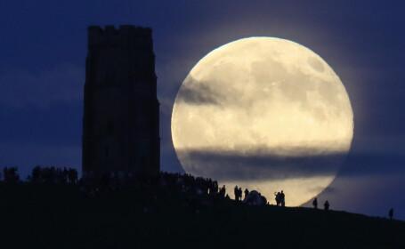 Luna plina, de culoare capsunei, deasupra Glastonbury Tor, la Solstitiul de vara