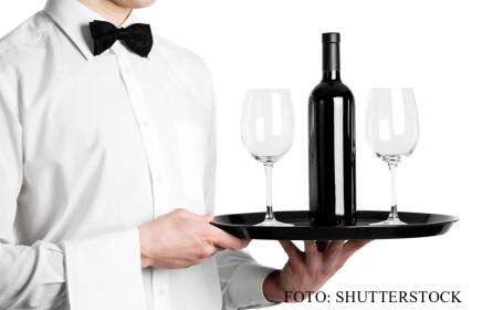 chelner cu sticla de vin si pahare pe tava