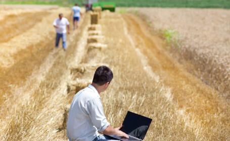 barbat cu laptopul in brate pe camp