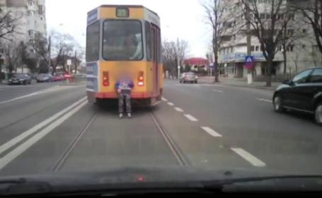 Copil asezat pe tamburul unui tramvai care circula cu viteza, filmat cu camera de bord. Cum reactioneaza soferul