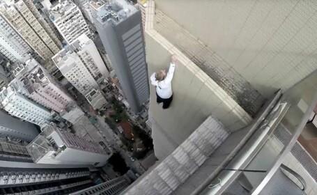 Cel mai infricosator antrenament din lume: un tanar a stat atarnat cu o singura mana de marginea unui zgarie-nori. VIDEO