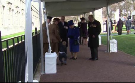 Un copil s-a lasat convins cu greu sa ii ofere Reginei Elisabeta un buchet de flori. Baiatul a incercat sa fuga