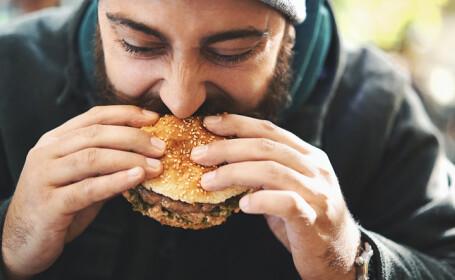 barbat mancand un burger