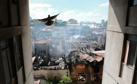 Un porumbel zboară peste un cartier mistuit de flăcări, în orașul filipinez Quezon