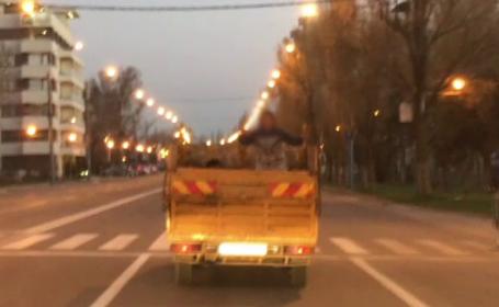 Copil plimbat de tatăl său în bena camionului, prin Constanţa. Era să cadă în mers