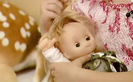 fetita cu papusa in brate
