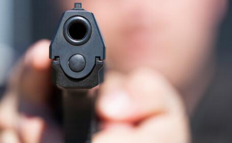 barbat cu un pistol in mana