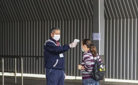 Un agent de paza de la un supermarket masoara temperatura clientilor la intrarea in magazin