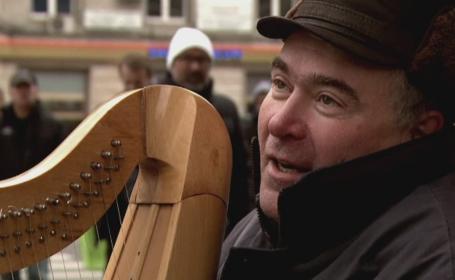 Un basarabean canta la harpa in centrul Bucurestiul pentru a-si aduce familia in Romania. POVESTEA de viata a lui Leonid