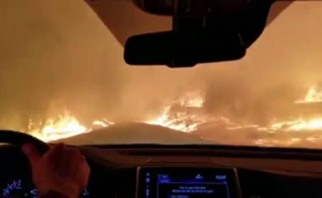 Filmare impresionantă: o familie conduce printre flăcări și se roagă să scape. VIDEO