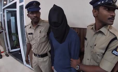 Români arestați pentru terorism cibernetic în India, prezentați cu cagule pe cap