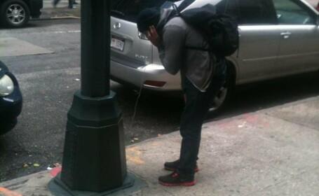 barbat vorbeste la mobilul conectat la un stalp de lumina