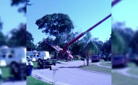 O macara adusa sa indeparteze un copac doborat de furtuna s-a prabusit peste o casa si cateva masini, in Florida. VIDEO