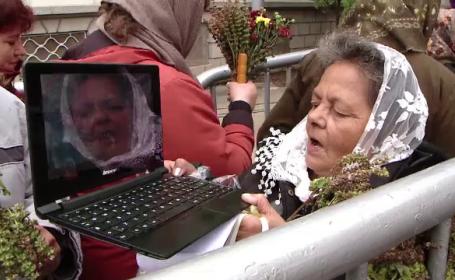 Scene ireale la pelerinajul de la Iasi. O femeie se pozeaza sarutand moastele Sf. Parascheva cu laptopul: \