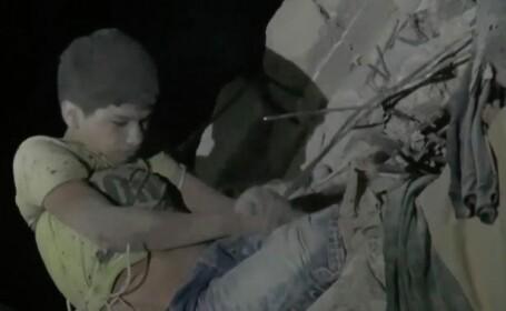 Noi imagini tulburatoare in Siria. Ce scria pe tricoul unui baiat care atarna la geamul unei cladiri bombardate. VIDEO