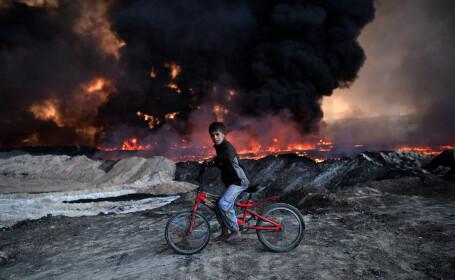 Un baiat pe bicicleta se opreste langa un camp petrolier incendiat de ISIS, in Mosul