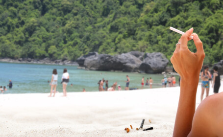 turista care fumeaza pe plaja
