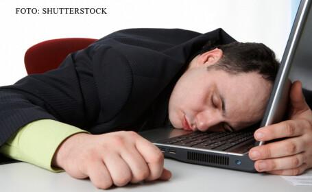 barbat care doarme cu capul pe laptop