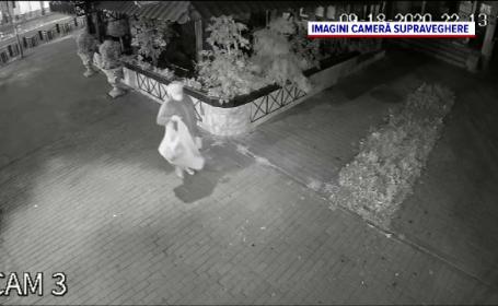 O femeie fură flori din fața unei terase