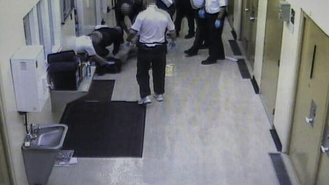 Gardienii se bucură în timp ce un deținut bătut este transportat la spital