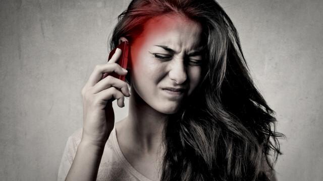 femeie care vorbeste la telefon si o doare capul